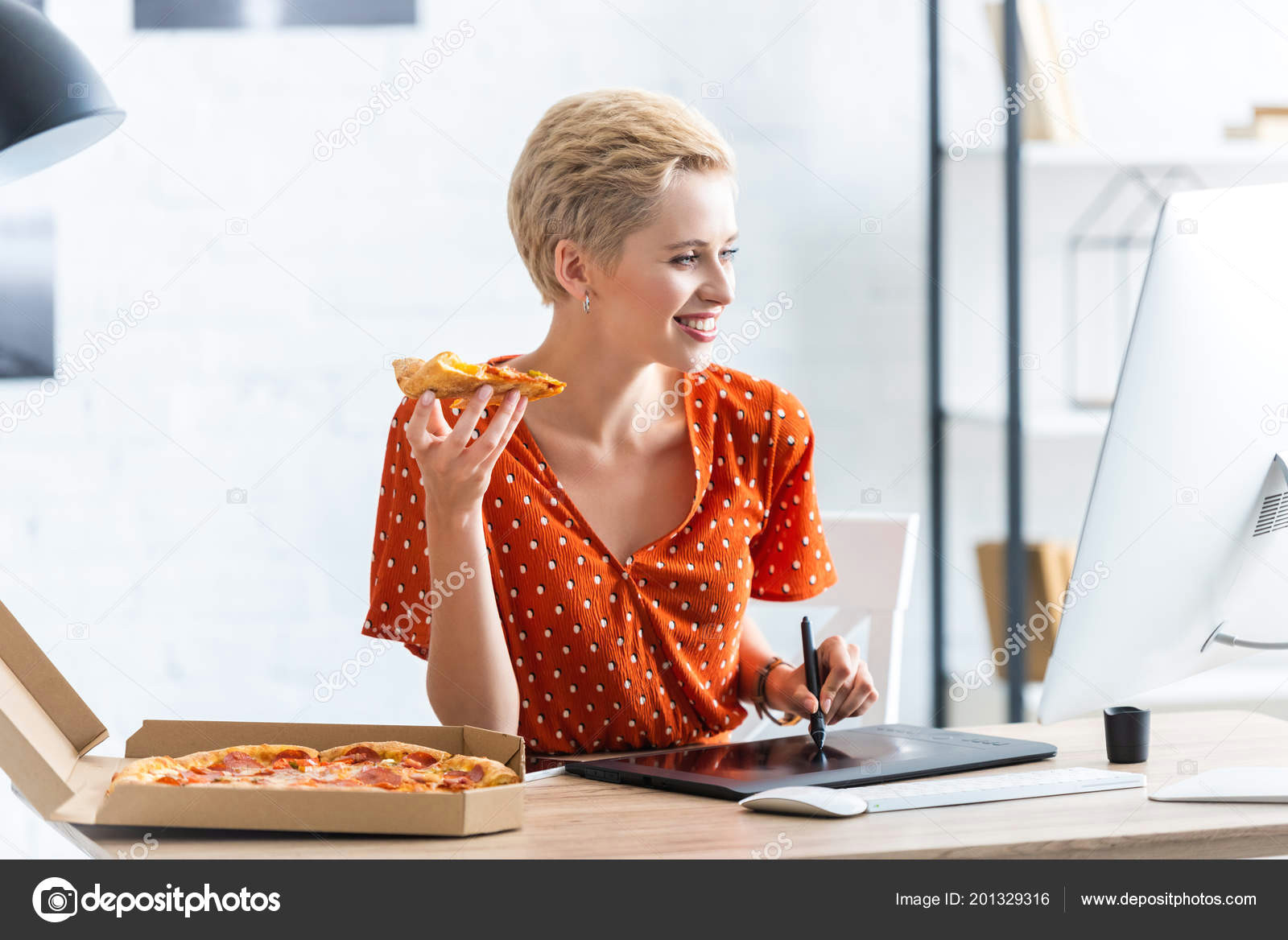 smiling female freelancer eating pizza and drawing on graphic tablet at home office zdja cie od edzbarzhyvetsky