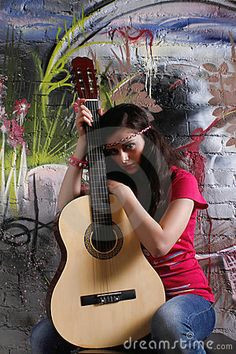hippie girl with guitar in front of a graffiti brick wall photography classes girl photography
