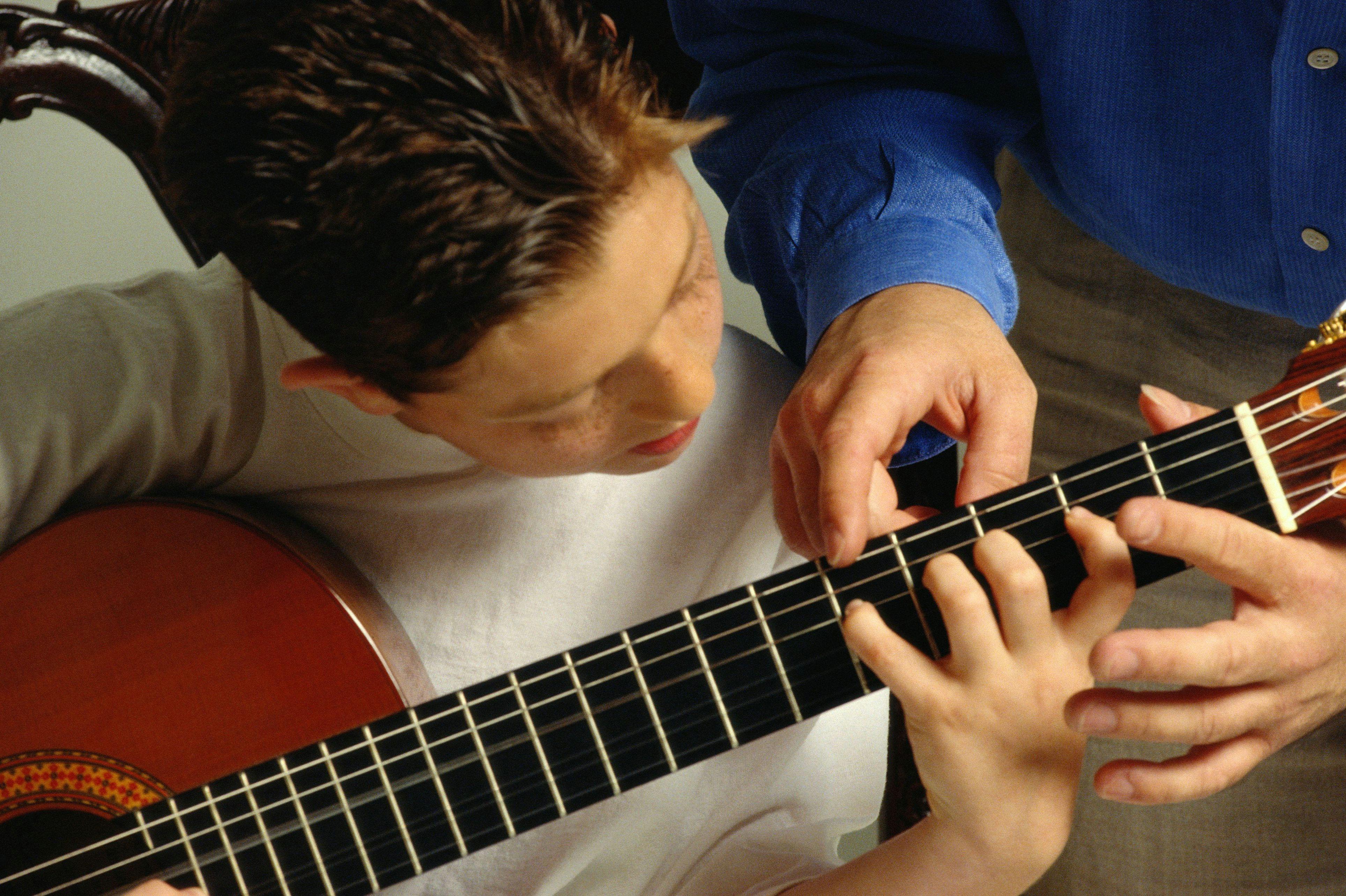 teaching young boy guitar 10140747 58e5285b3df78c5162b342ba 5b7c2b5146e0fb008213b3bc jpg