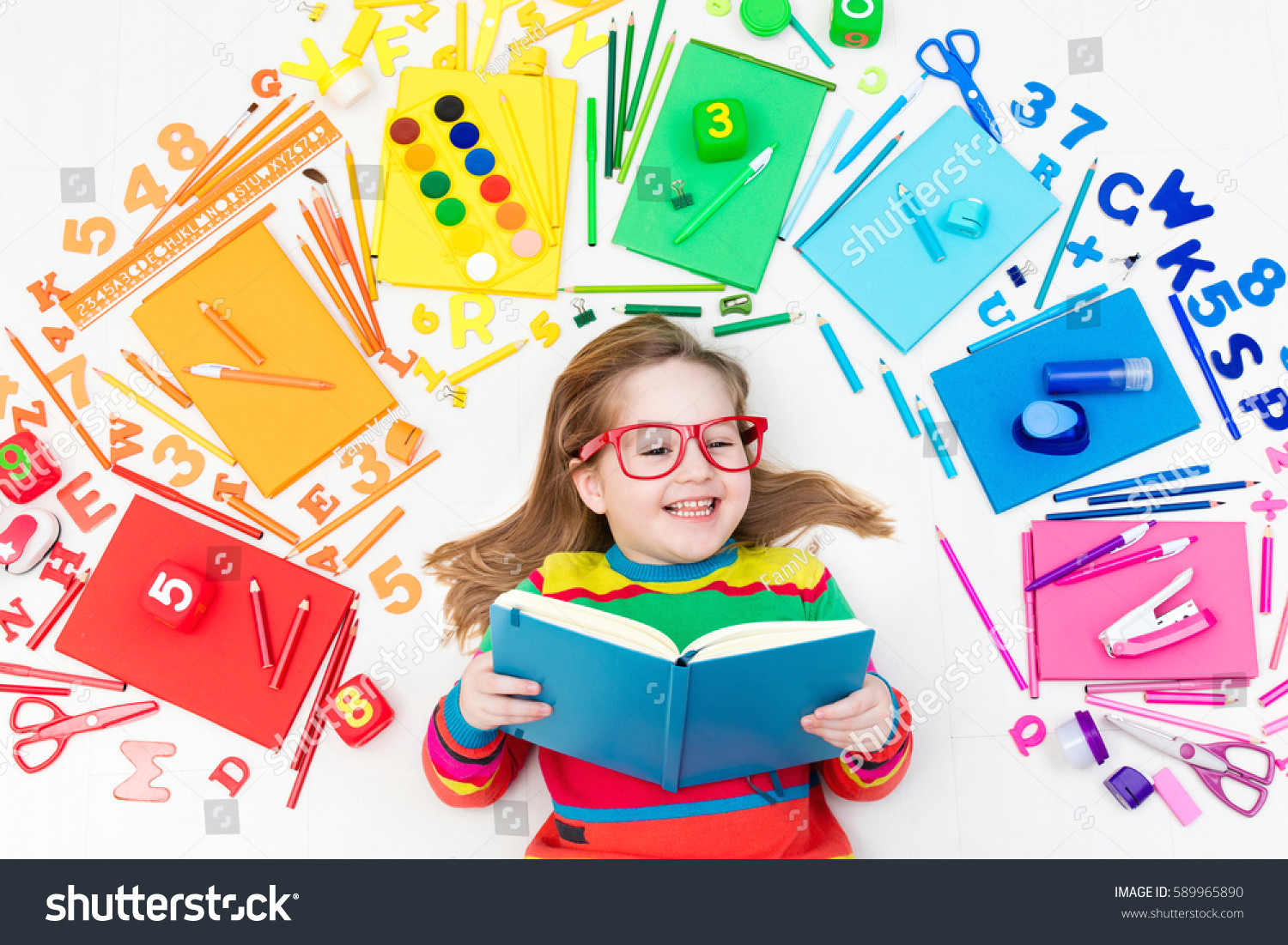 little girl with school supplies books drawing and painting tools and materials happy