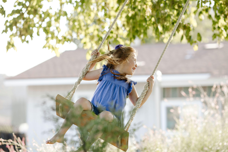 happy girl swinging on rope swing at front yard 961511476 5bc3ec70c9e77c00512ebd85 jpg
