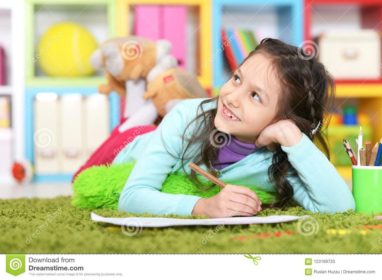 cute little girl drawing lying cute little girl drawing lying floor green carpet home 123169733 jpg