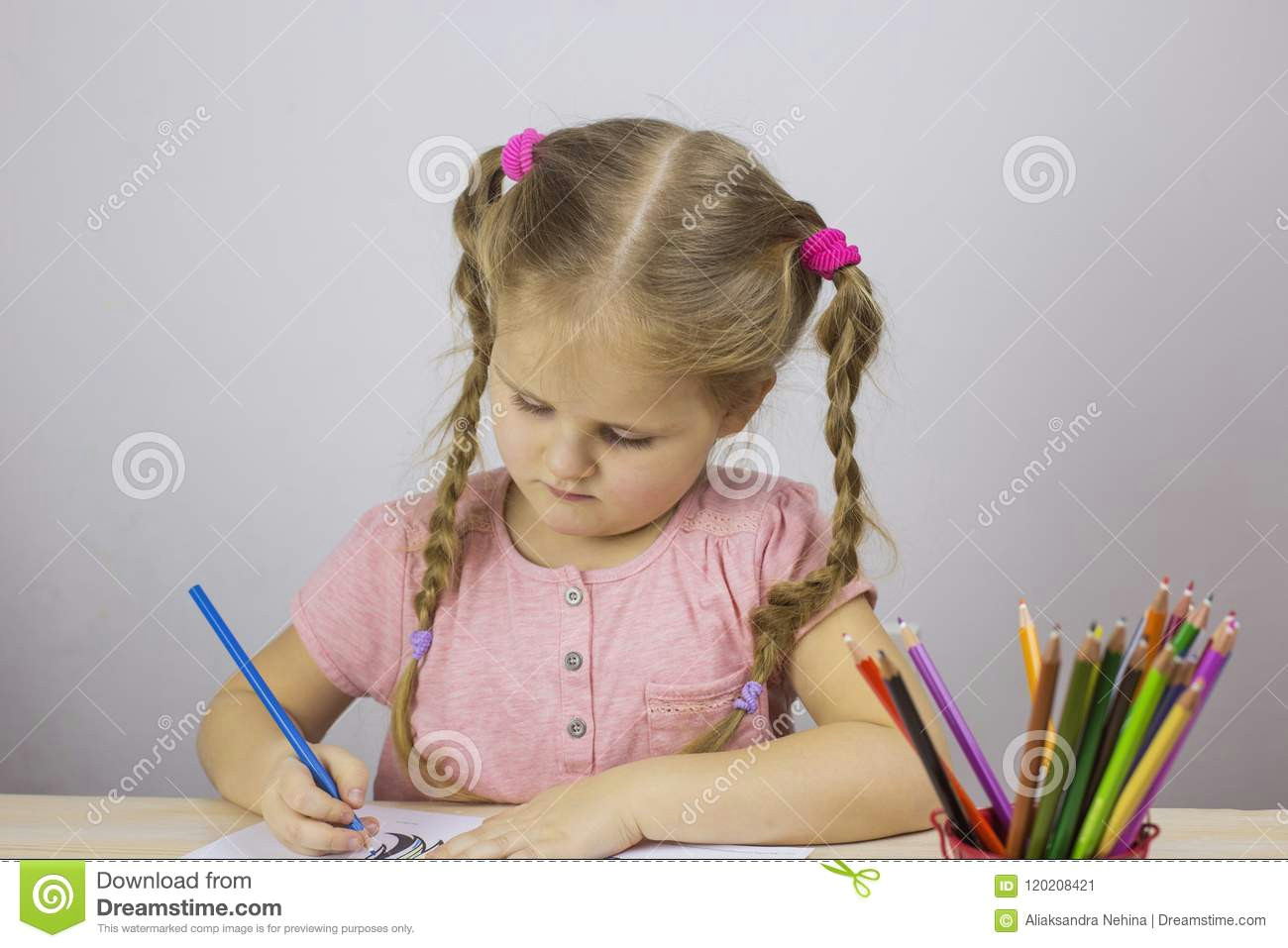 young girl draws colored pencils education concept young girl draws colored pencils table 120208421 jpg